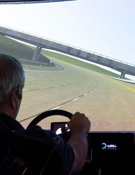Driver using Millbrook's virtual proving ground simulator showing digital twin of the test tracks