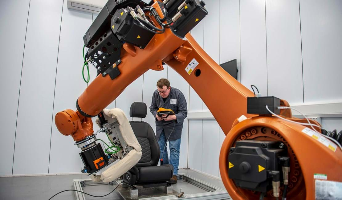 Automotive seat testing laboratory engineer at Millbrook operating KUKA robot